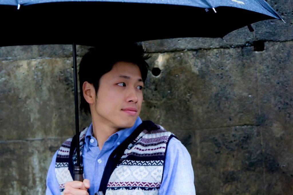 雨の日に傘をさしている男性