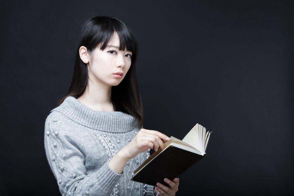 本を見ながら冷ややかな視線を送る女性