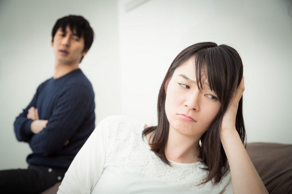 怒らせた妻を見つめて途方に暮れる男性