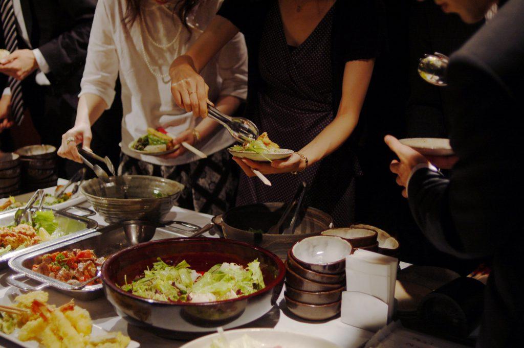 ビュッフェ式でサラダを取り分ける女性たち