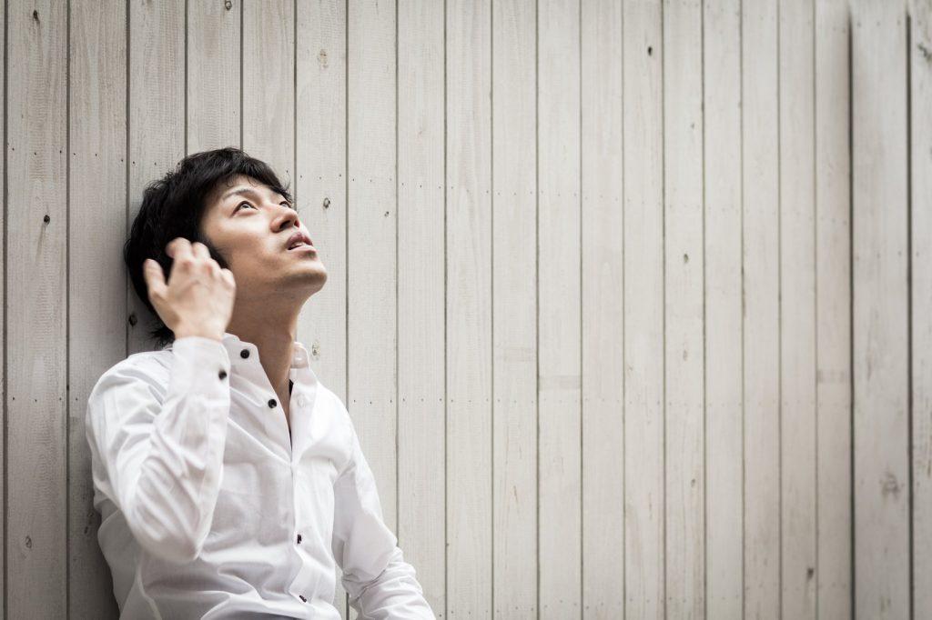 電話をしながら空を見上げる男性