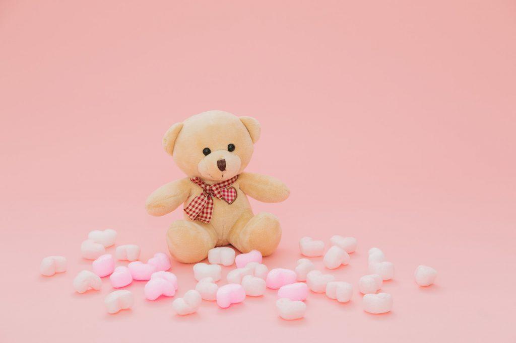 ピンク色の部屋にあるクマのぬいぐるみ