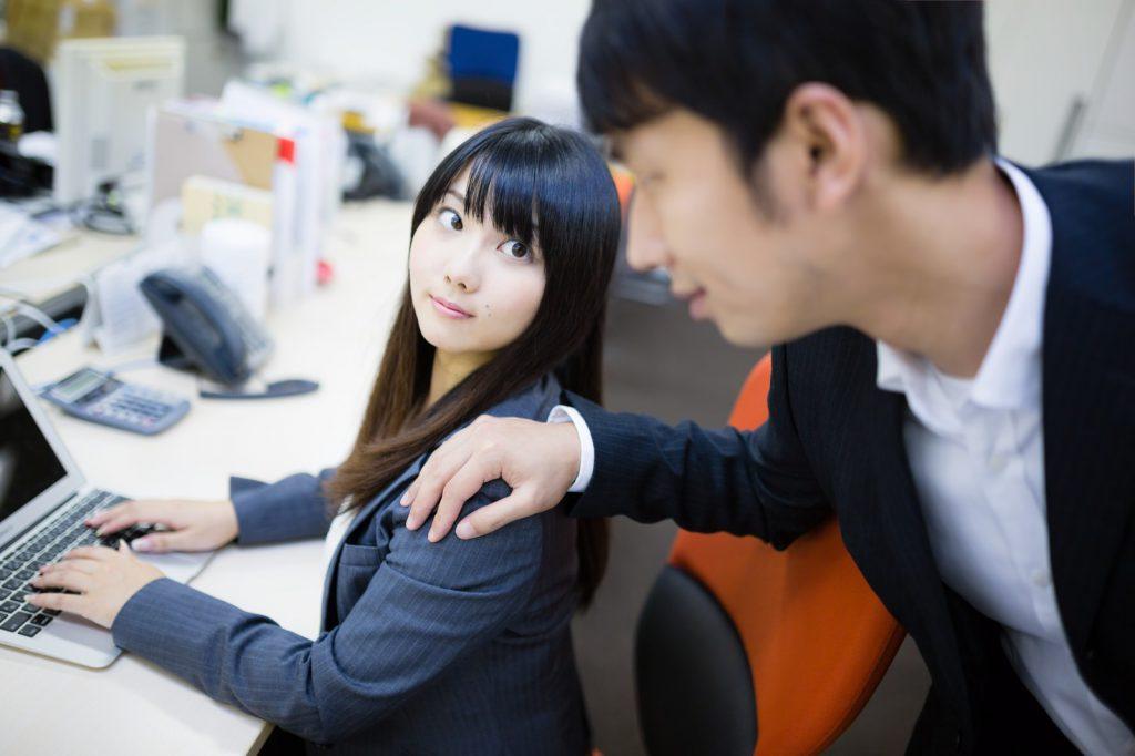 オフィスで働く女性の肩をたたく男性