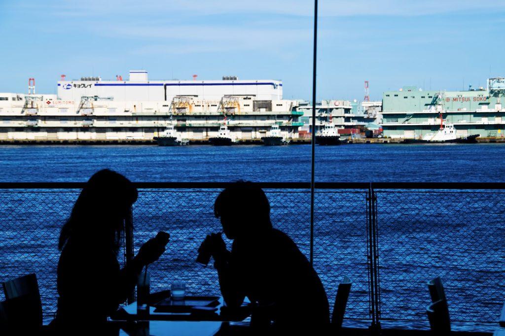 海が見えるカフェで食事を楽しむカップル