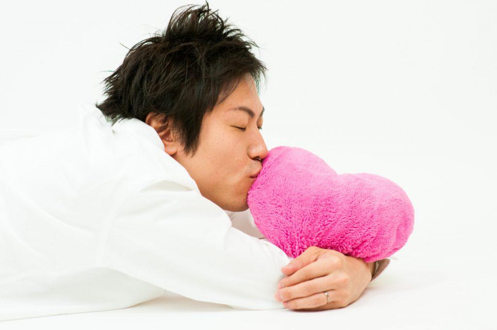 ハートのぬいぐるみにキスする男性