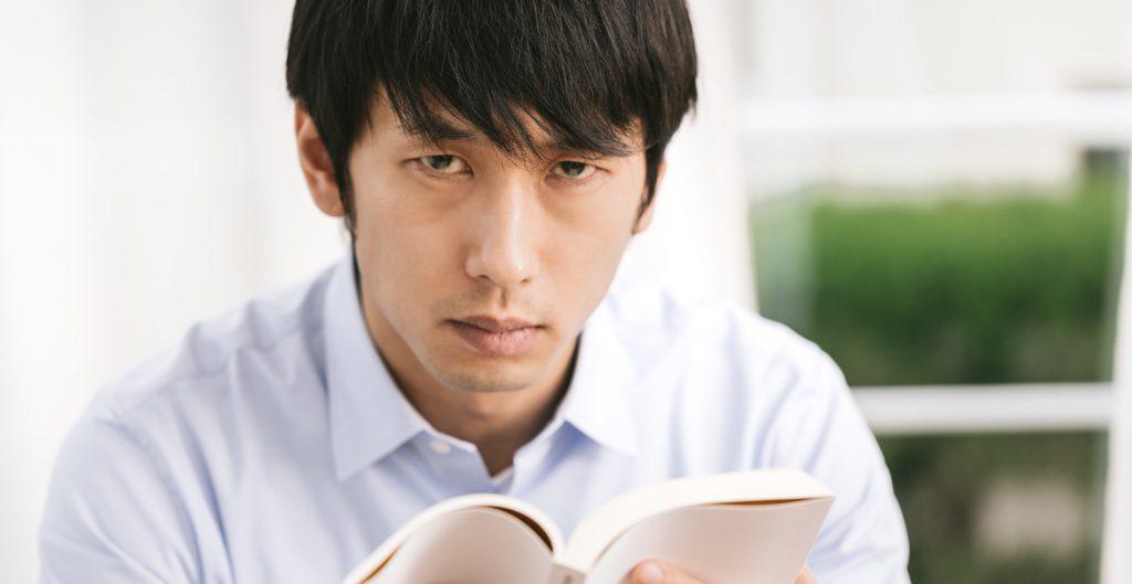 読書をしながらにらみを利かせる男性