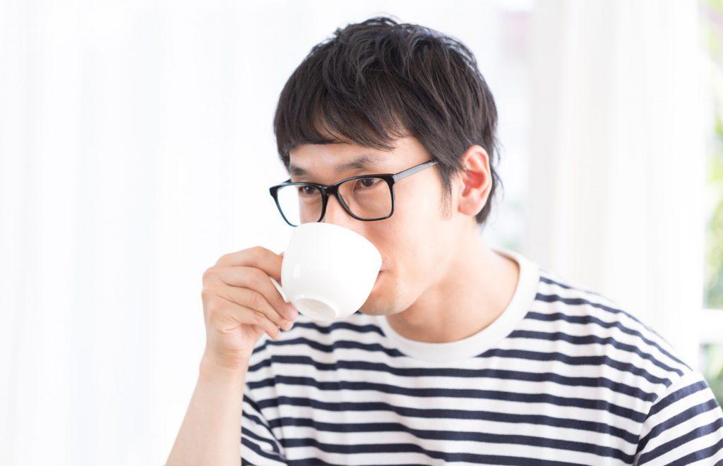 カップでコーヒーをすする男性