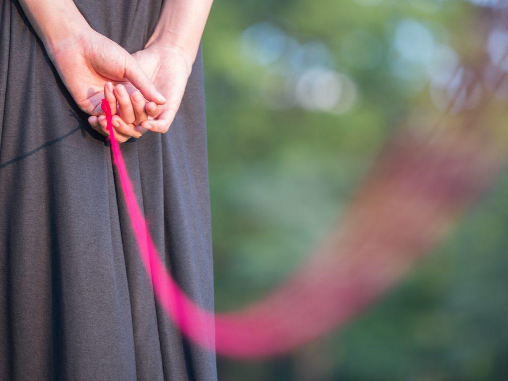 赤い糸を持つセーラー服の女性