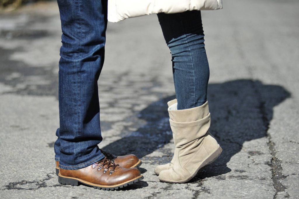 背伸びしている女性と男性の足元