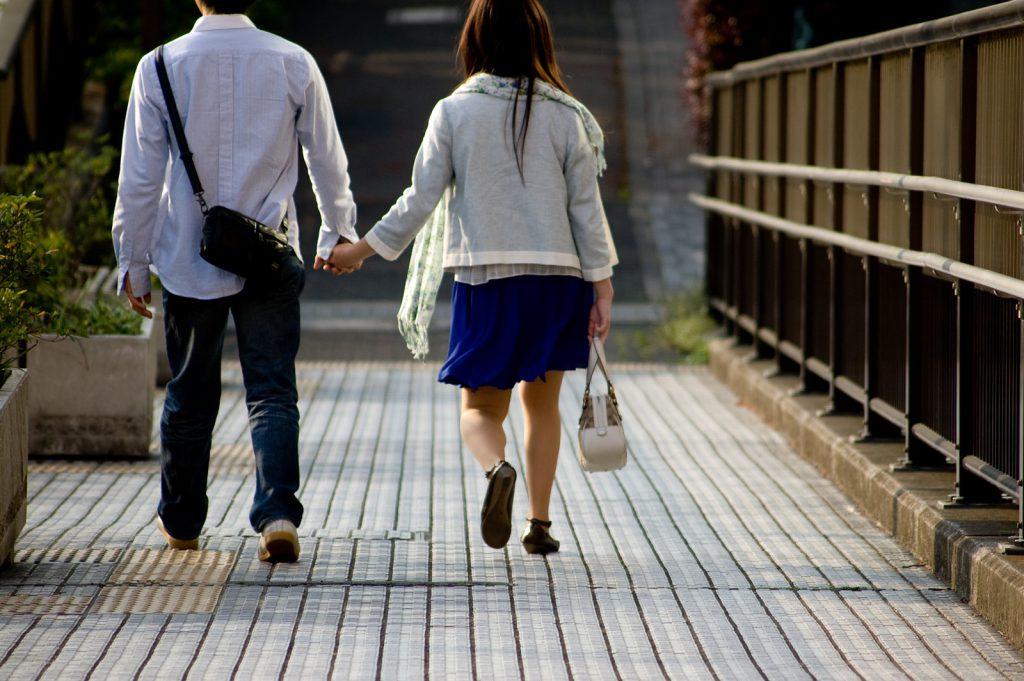 手をつなぐスーパー帰りのカップル