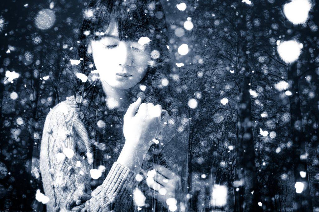 雪が降る中悲しむ女性