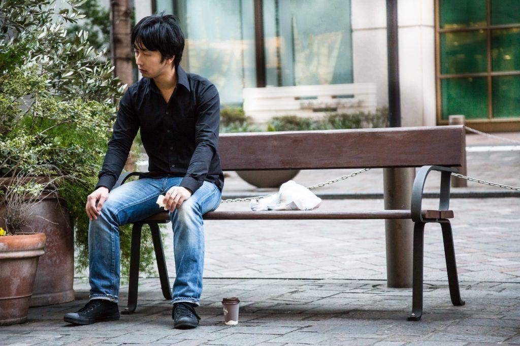 一人きりでベンチに座る男性