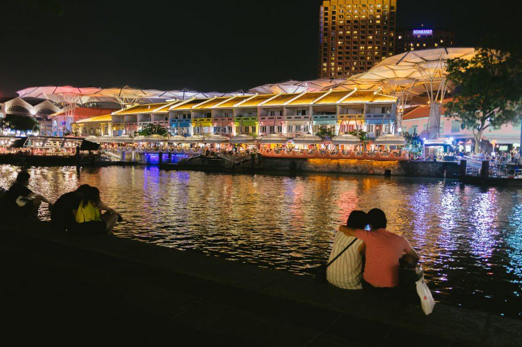夜に屋形船を河原で見るカップル