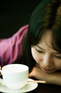 下を見つめる女性とコーヒーカップ