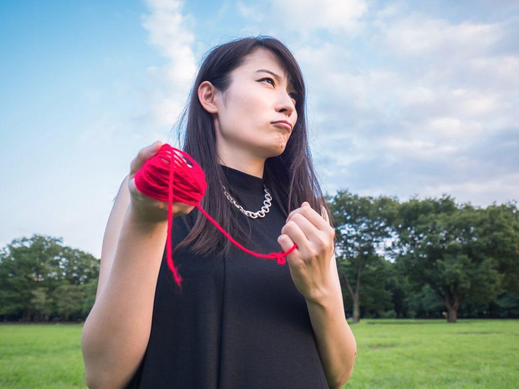 赤い糸を胸に持ち決意を新たにする女性