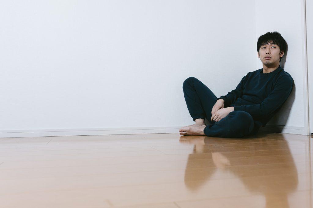 部屋で地べたに座り胡坐をかく男性