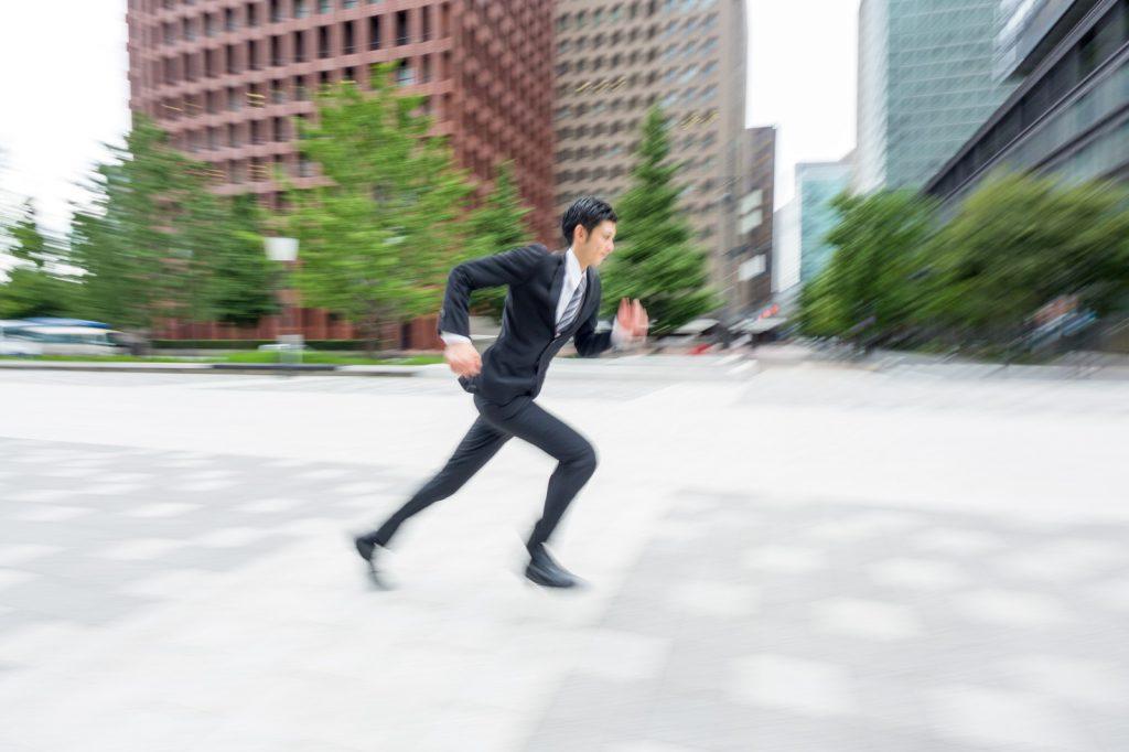 走るスーツ姿の男性