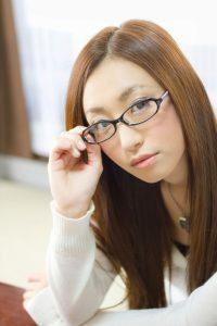 眼鏡を上にあげ挑発する女性