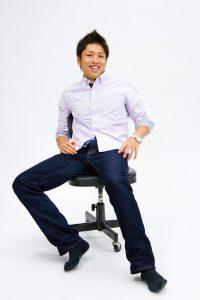 椅子に座りながら笑顔で話す男性