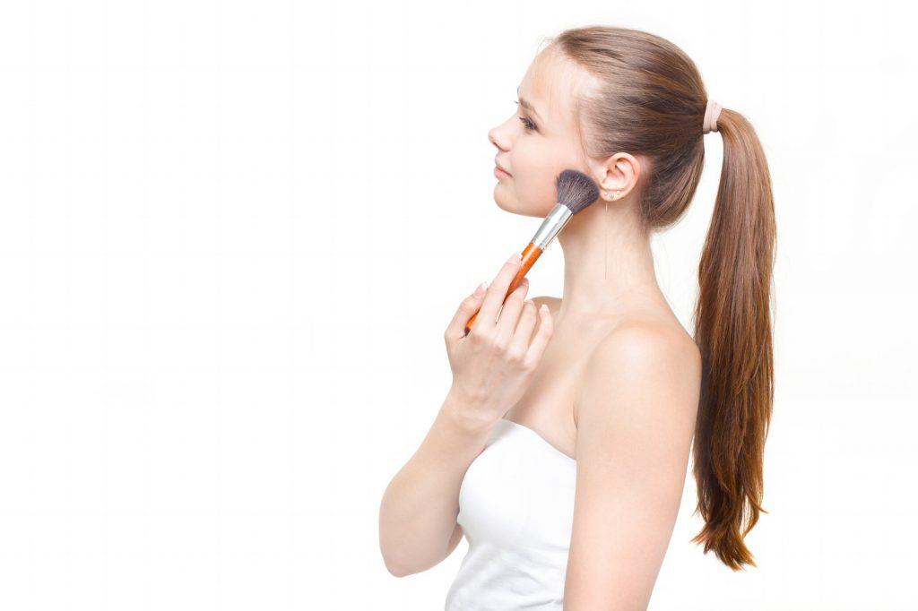 顔にファンデーションを塗る女性