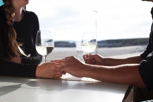 テーブルの上で手をつなぐカップル