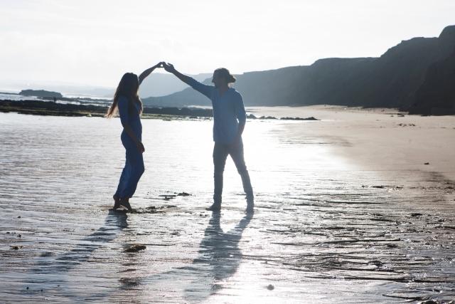 波打ち際で手をつなぐカップル