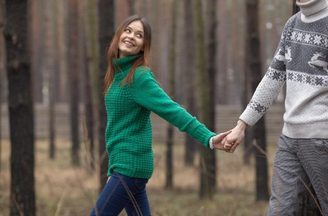 手をつなぎながら森林を歩くカップル