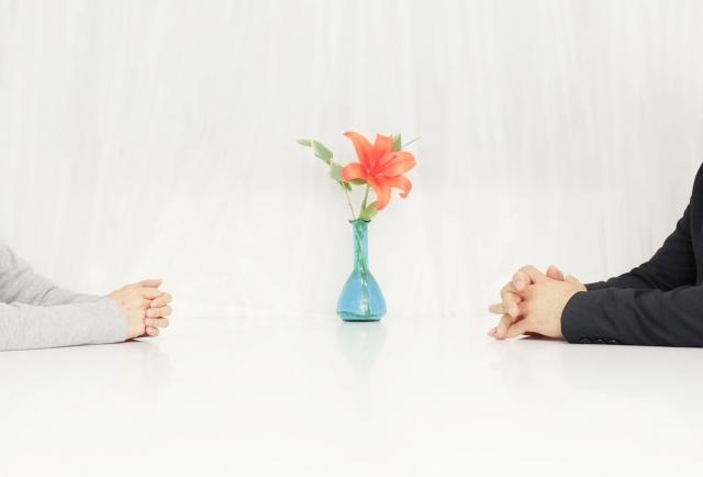 花瓶越しに話し合う男女