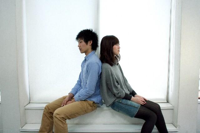 窓際に背中合わせで座るカップル