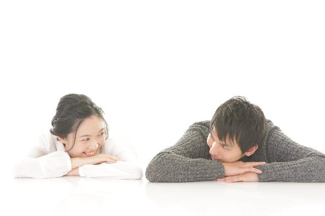 うつぶせになりながら笑いあうカップル