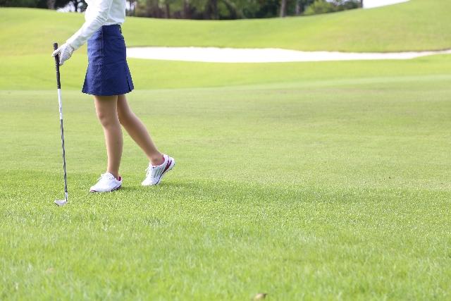 コースでゴルフクラブを持つ女性