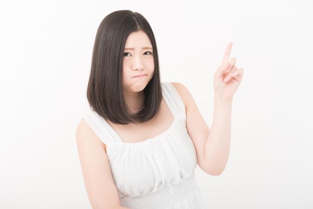 人差し指を上にして頬を膨らませる女性