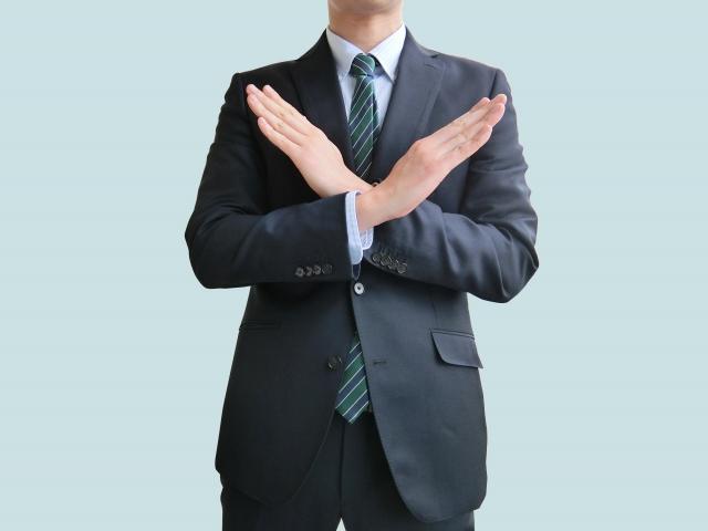 腕の前でバツ印を作るスーツ姿の男性