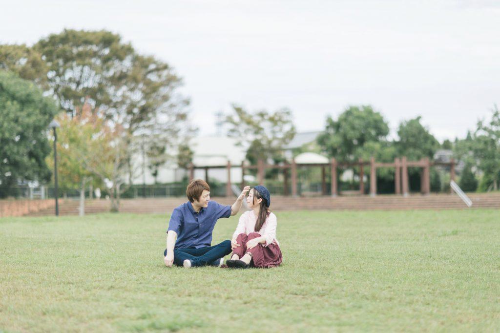 草原でじゃれあうカップル