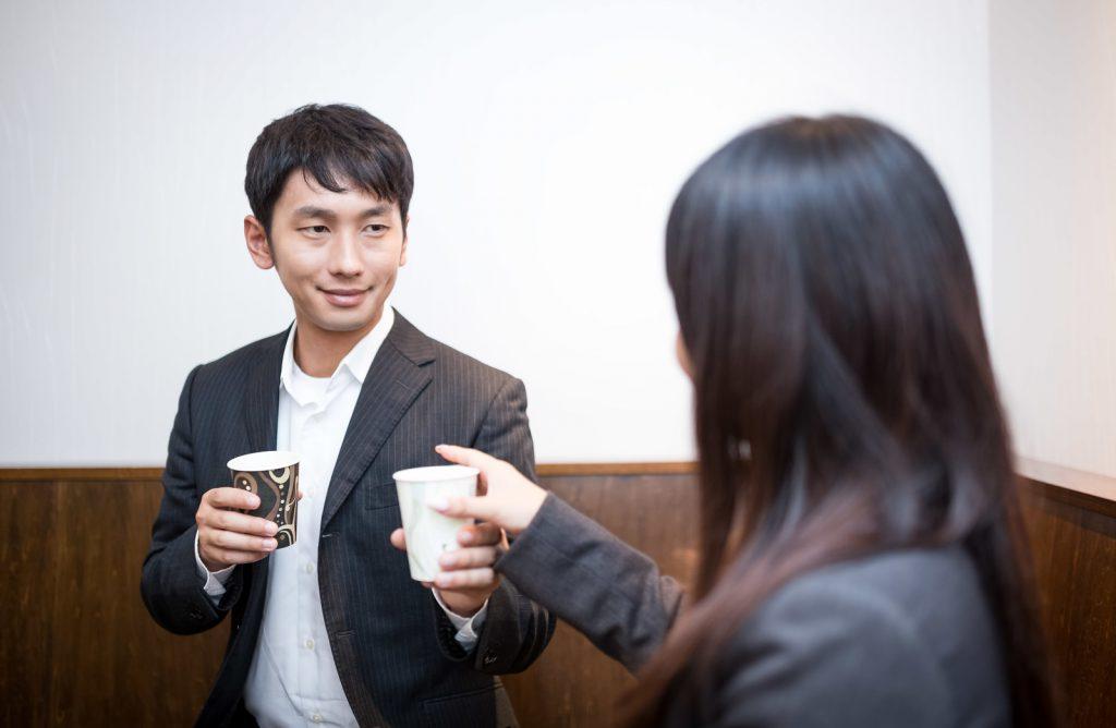 緊張した面持ちで女性にコーヒーを渡す男性