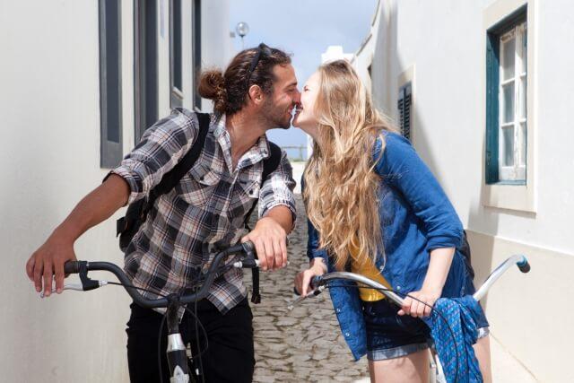 自転車を引きながらキスするカップル