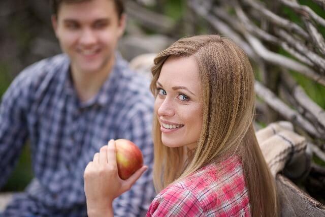 リンゴを持ち笑顔で振り向く女性