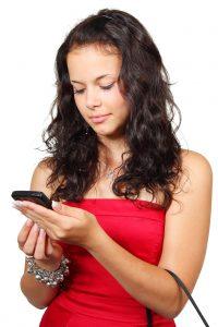 メッセージを送る赤いワンピースの女性