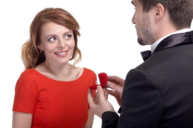 バラを持って女性を口説く男性