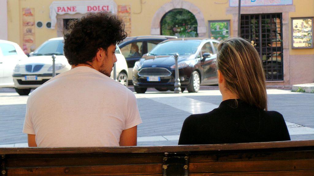 ベンチで話し合うカップル