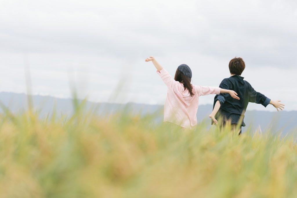 草原で背伸びするカップル