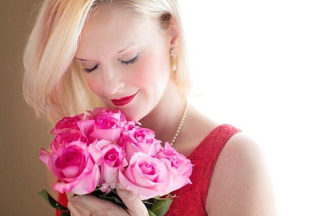 花のにおいをかぐ女性