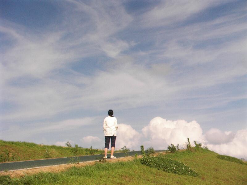 丘の上で空を見上げ立ちすくむ女性