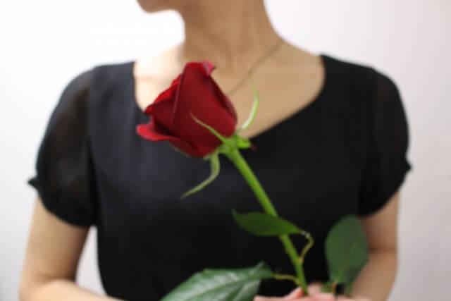バラを持つ黒いTシャツを着た女性