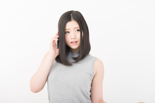 目をそらし髪をかき上げる女性