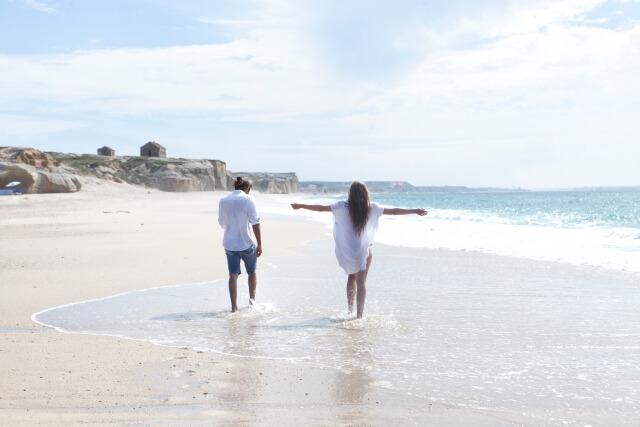 海辺で水に濡れながら歩くカップル