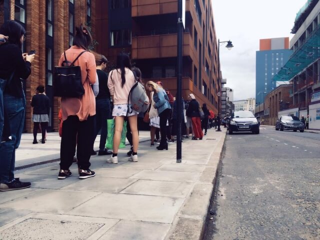 バスの列に並ぶ人々