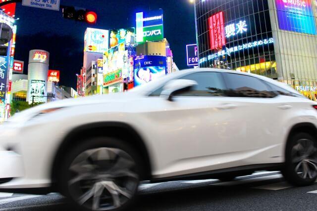 ネオン街を走る白いスポーツカー