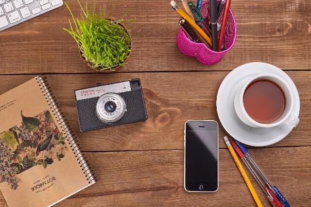 カフェの机にあるコーヒーやカメラ