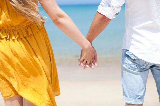 砂浜で手をつなぐカップル